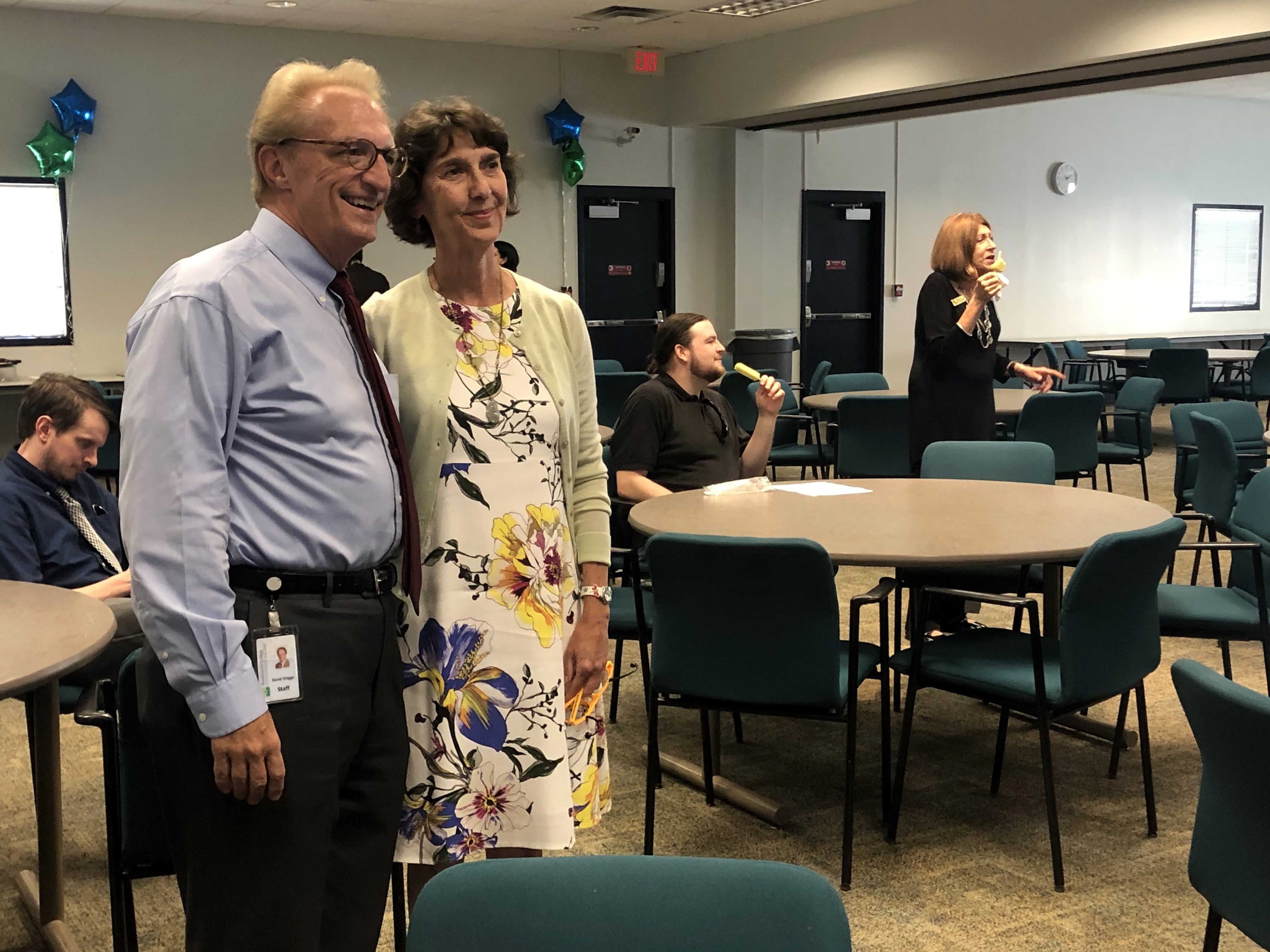 Photo by Jacob Vaughn | David Griggs (left), adjunct professor of criminology, and Carrie Schweitzer, director of sustainability, pose for a photo at her retirement party Aug. 28.
