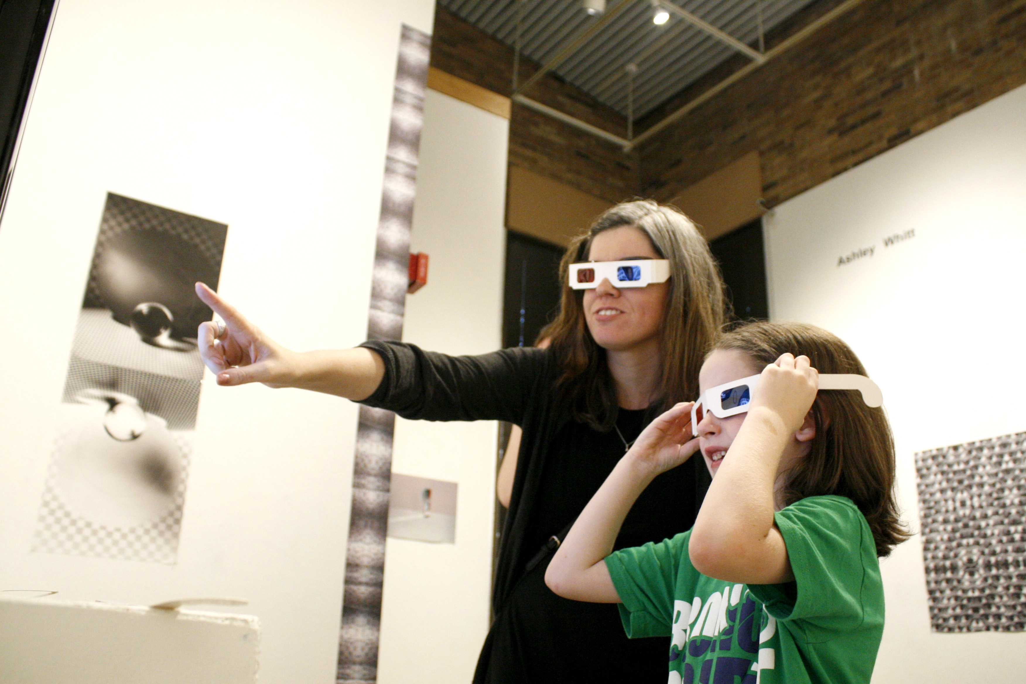 <strong>Photo by Matthew Brown |</strong> Artist Ashley Whitt and gallery attendee Jack Browning look through 3D glasses at works featured in Whitt's exhibition