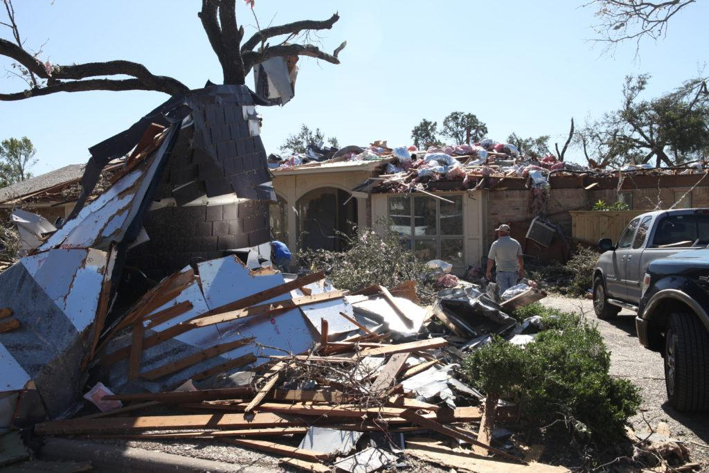 <strong>Photo by Malen Blackmon |</strong> A resident walks among the aftermath of an EF-3 tornado that swept through Preston Hollow Oct. 23