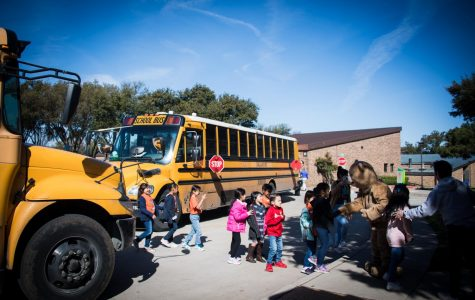 School children walk off a bus