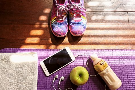 Tenis shoes, an iPhone, apple and a bottle over towels