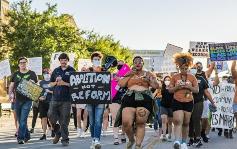 A group of activists march through a Denton street.