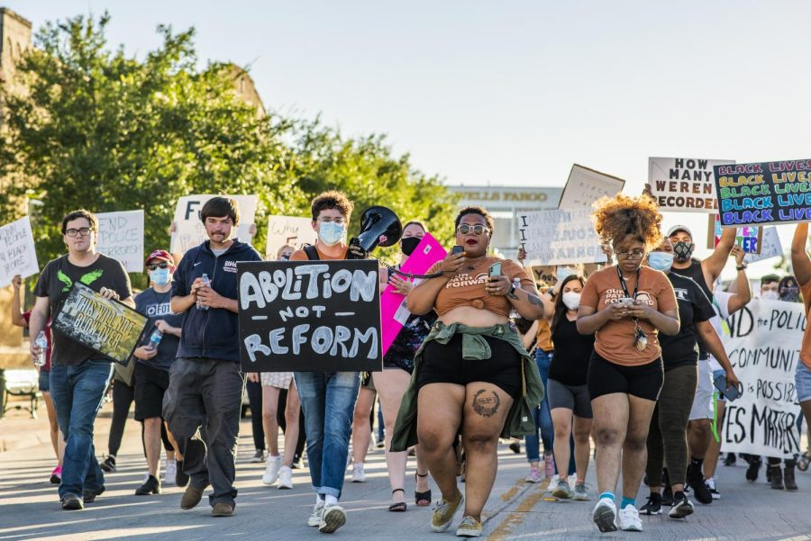 A group of activists march through a Denton street.