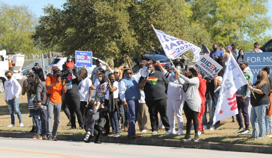 Dozens of supporters gather on the side of the road to see Democratic vice presidential nominee Kamala Harris, during a campaign stop Oct. 30 in Fort Worth.