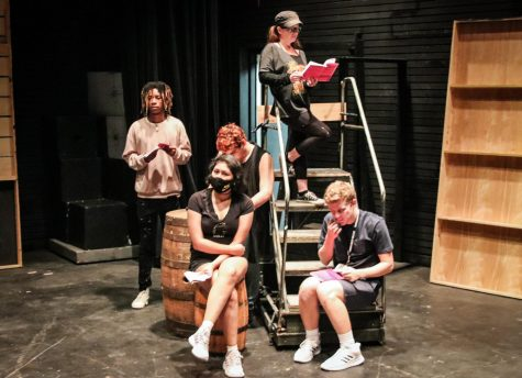 Cast members in various sitting positions at Black Box Theater